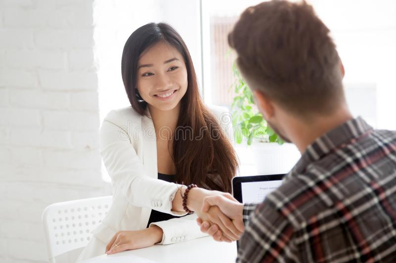 Male hr shaking hand of smiling Asian work candidate stock image