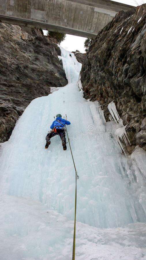 Male ice climber in a blue jacket climbs a frozen waterfall in the Avers Valley in the Swiss Alps stock images