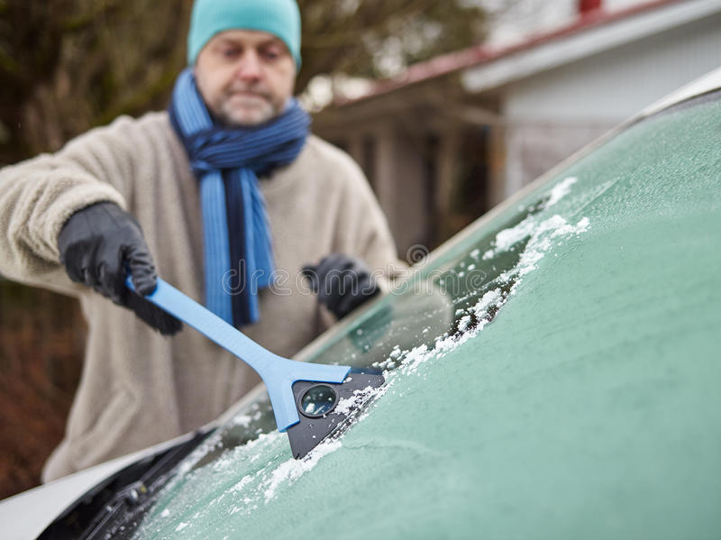 Male and ice scraper. The mid adult man cleans a frozen windshield - focus on ice scraper, horizon format royalty free stock images