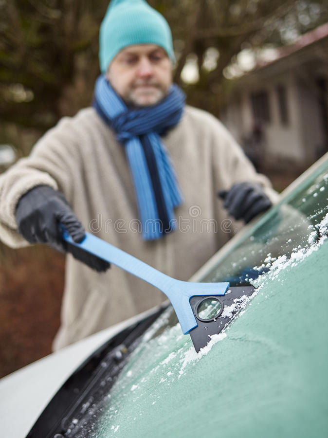 Male and ice scraper. The mid adult man cleans a frozen windshield - focus on ice scraper, vertical format royalty free stock photos