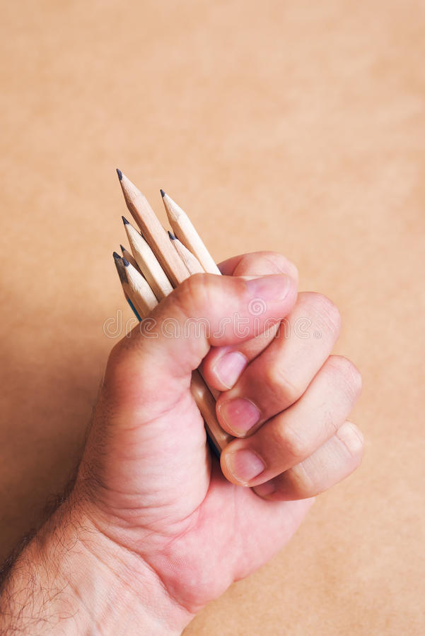 Male illustrator and sketch artist with handful of pencils. Selective focus stock image