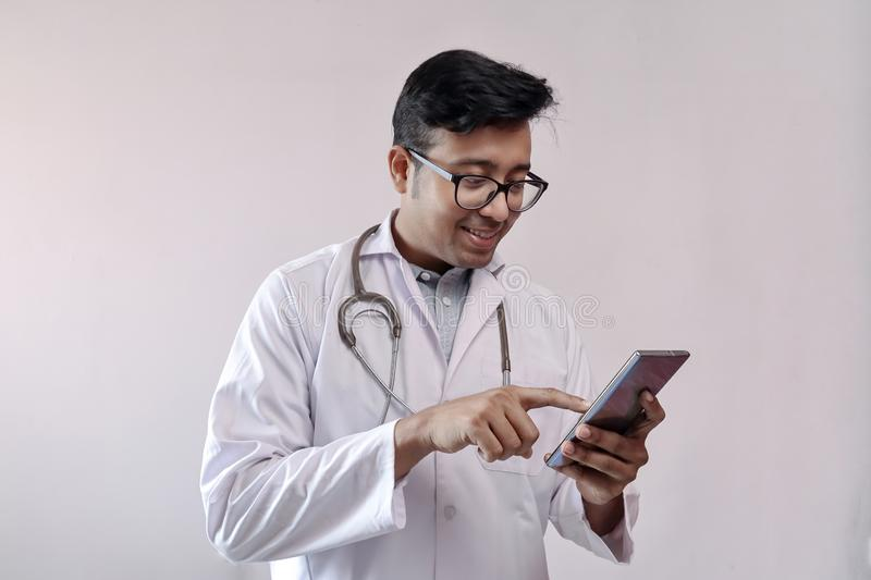 Male indian doctor in white coat and stethoscope touching smart phone royalty free stock photo