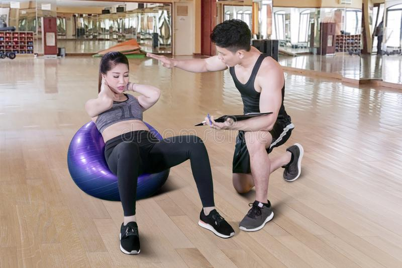 Male instruction helps a beginner to exercise. Picture of young male instruction helps a beginner to exercising her abdominal with yoga ball in the royalty free stock photos