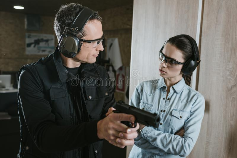 Male instructor describing gun to female client. In shooting gallery royalty free stock photo