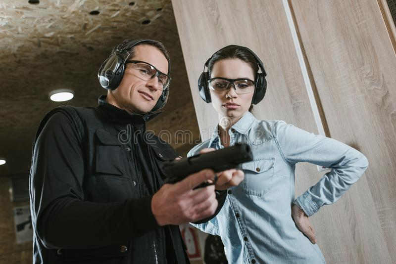 Male instructor describing pistol to female client. In shooting gallery stock image