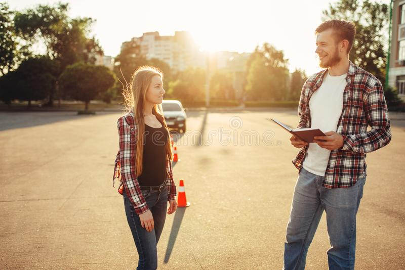 Male instructor and female student, driving school stock image