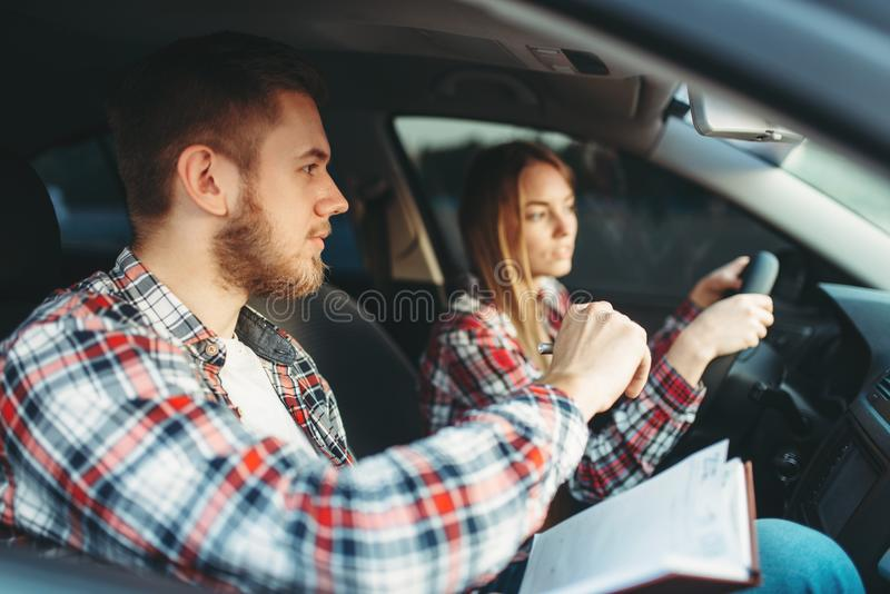 Male instructor and female student, driving lesson royalty free stock photography