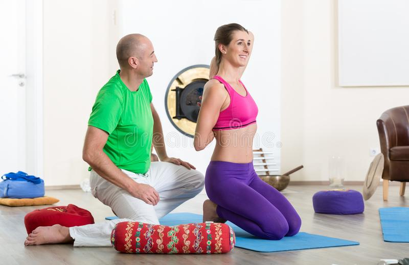 Man looking at woman doing yoga pose stock images