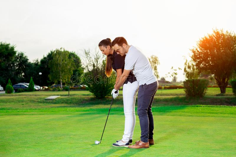 Male instructor showing woman to play golf royalty free stock photography