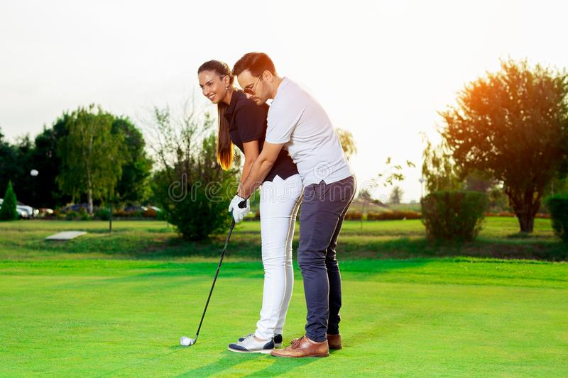 Male instructor showing woman to play golf stock photos