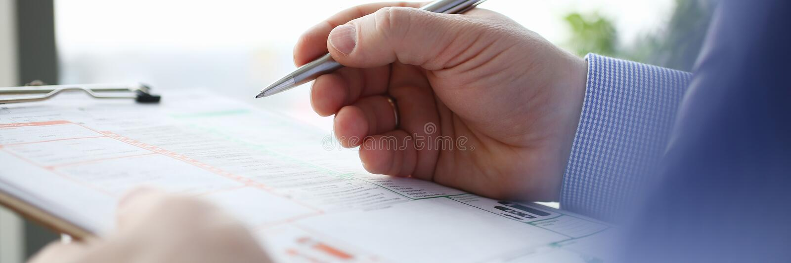 Male insurer hand hold silver pen stock photography