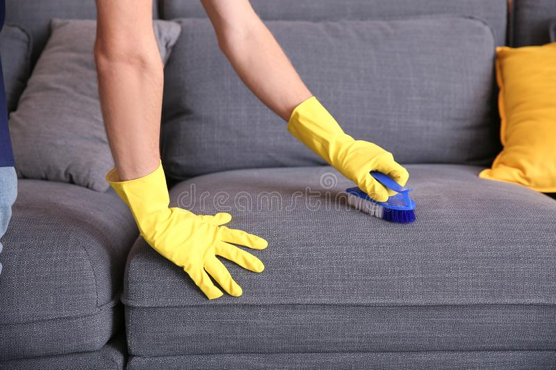 Male janitor cleaning furniture in flat royalty free stock photo