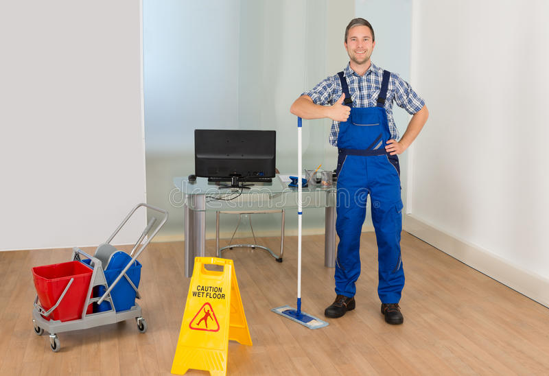 Male janitor gesturing thumbs up sign stock photos