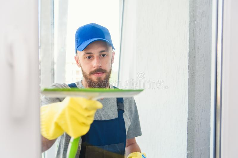 Male janitor using a squeegee to clean a window in an office wearing an apron and gloves as he works royalty free stock photo