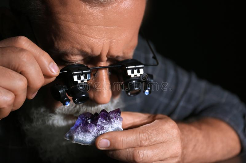 Male jeweler evaluating amethyst in workshop. Closeup view royalty free stock image