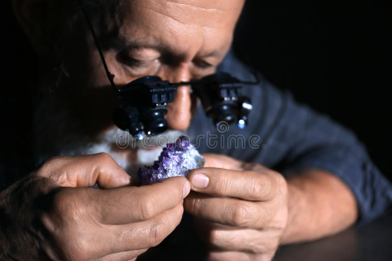 Male jeweler evaluating amethyst in workshop. Closeup view stock photo