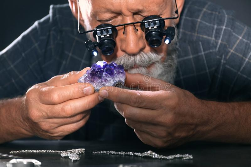 Male jeweler evaluating amethyst in workshop. Closeup view stock photos