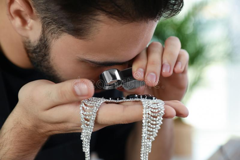 Male jeweler evaluating beautiful necklace in workshop. Closeup stock photography
