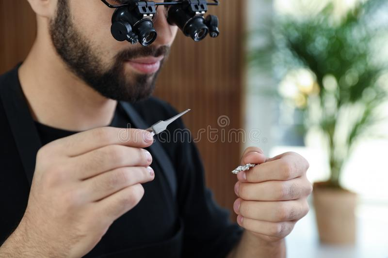 Male jeweler evaluating brooch in workshop. Closeup royalty free stock photo