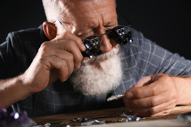 Male jeweler evaluating  brooch in workshop, closeup view stock photos