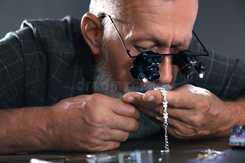 Male jeweler evaluating diamond bracelet in workshop. Closeup view stock photos