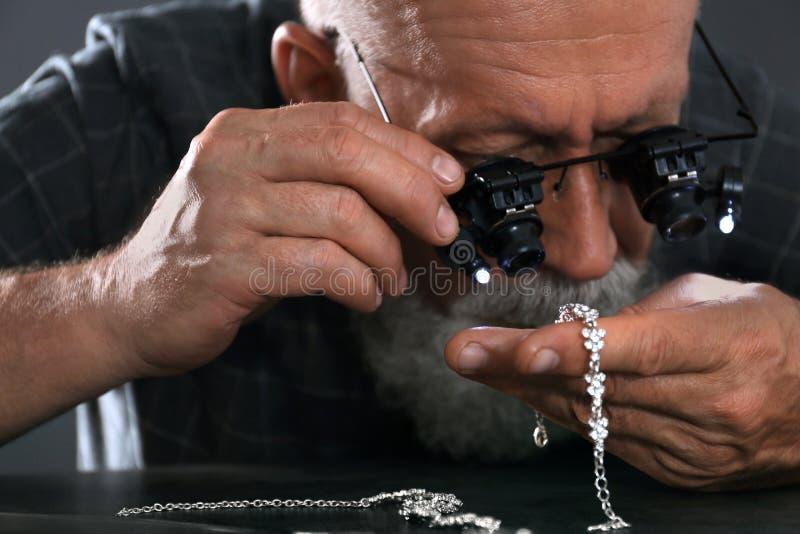 Male jeweler evaluating diamond bracelet in workshop. Closeup view stock photography