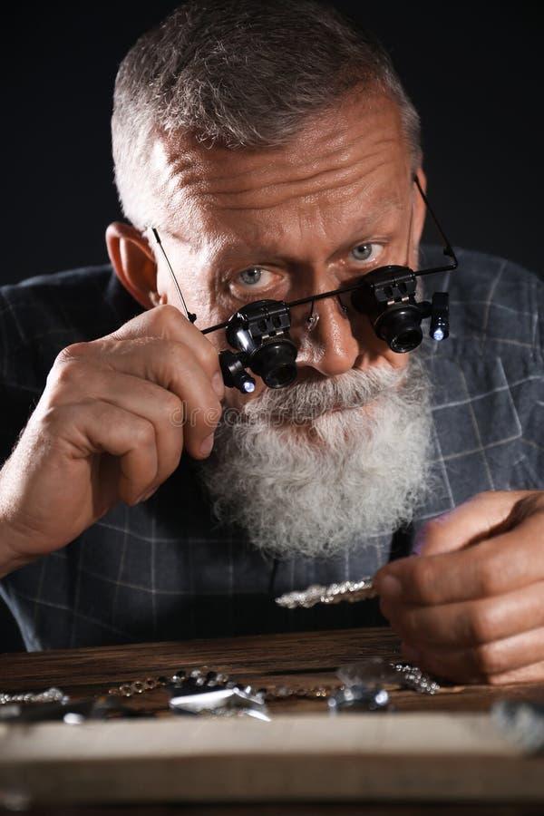 Male jeweler evaluating diamond brooch. In workshop stock photo