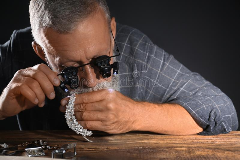 Male jeweler evaluating diamond necklace. In workshop stock photography