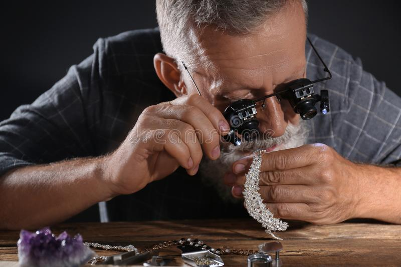 Male jeweler evaluating diamond necklace. In workshop royalty free stock photos