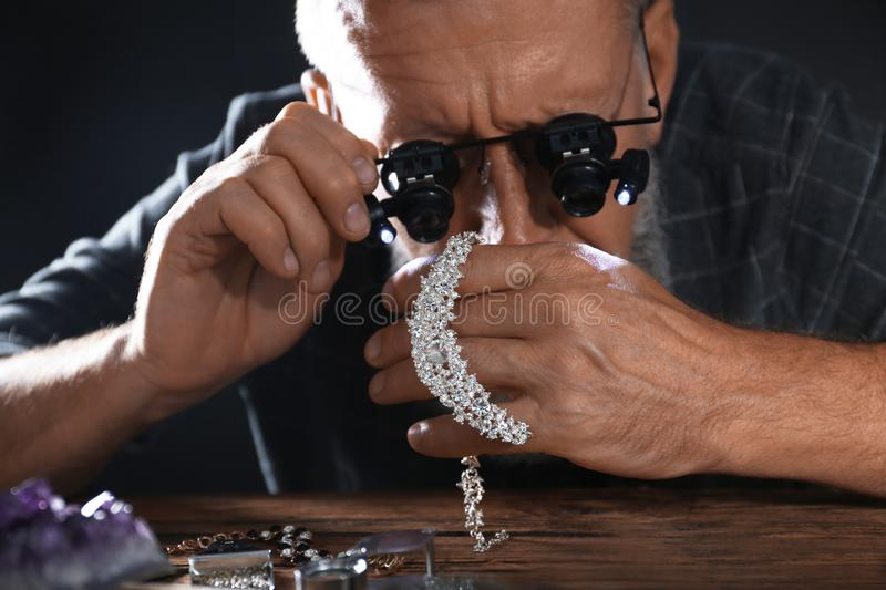 Male jeweler evaluating diamond necklace. In workshop royalty free stock image
