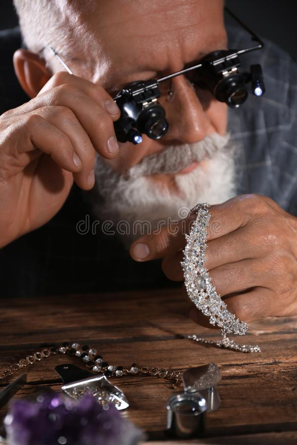Male jeweler evaluating diamond necklace. In workshop stock image