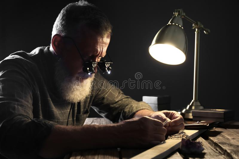 Male jeweler evaluating diamond ring. In workshop royalty free stock images