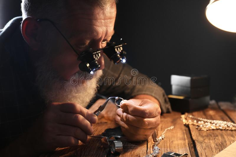 Male jeweler evaluating diamond ring. In workshop stock images