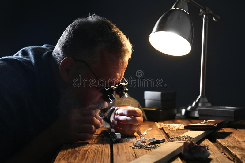 Male jeweler evaluating diamond ring. In workshop royalty free stock photos