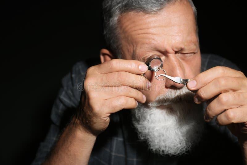 Male jeweler evaluating diamond ring. In workshop stock photo