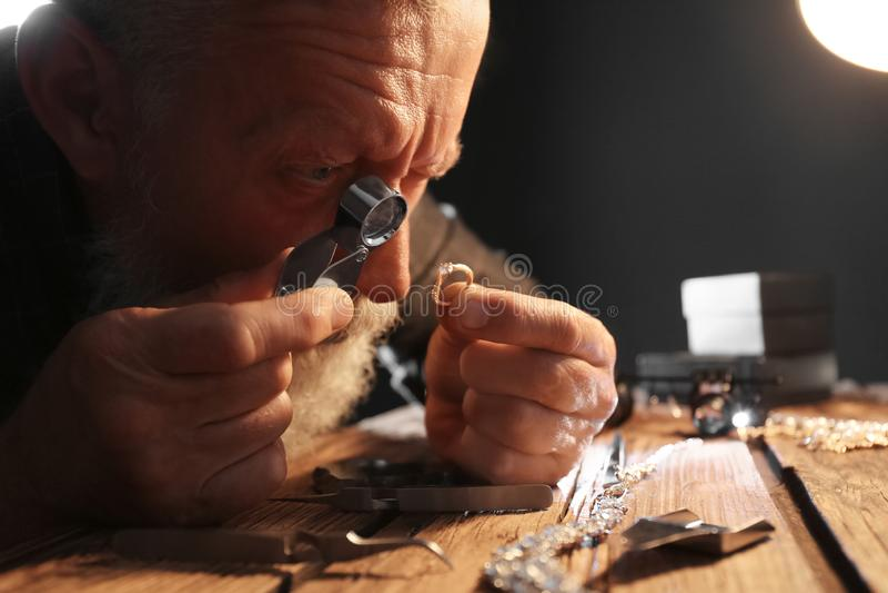 Male jeweler evaluating diamond ring. In workshop stock image