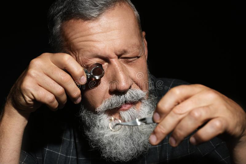 Male jeweler evaluating diamond ring in workshop, closeup. View stock image