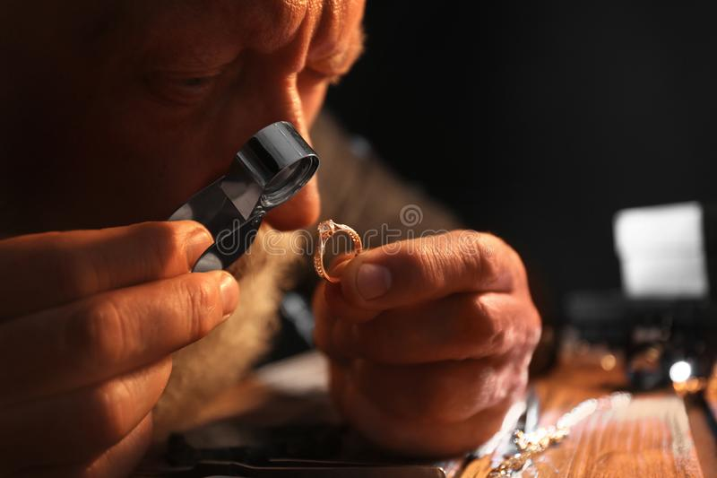 Male jeweler evaluating diamond ring in workshop, closeup. View royalty free stock photography