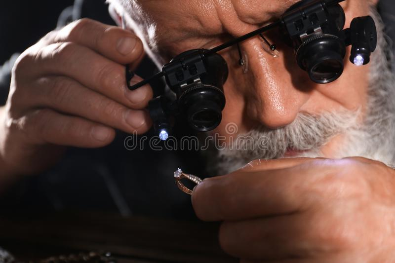 Male jeweler evaluating diamond ring in workshop. Closeup view royalty free stock images