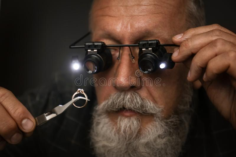Male jeweler evaluating diamond ring in workshop. Closeup view stock photography