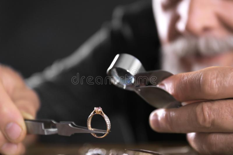 Male jeweler evaluating diamond ring in workshop stock photo