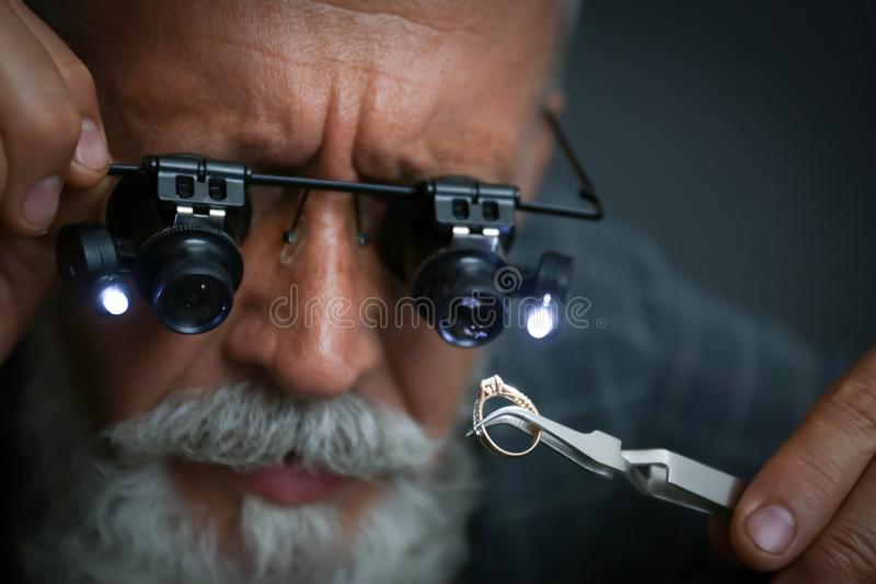 Male jeweler evaluating diamond ring in workshop. Closeup view royalty free stock photography