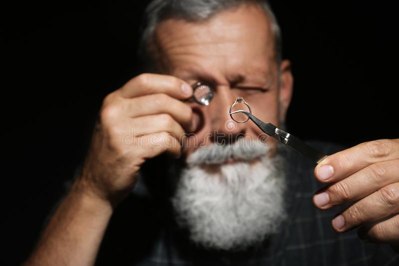 Male jeweler evaluating diamond ring in workshop stock photography