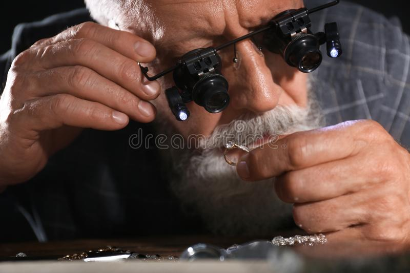 Male jeweler evaluating diamond ring in workshop. Closeup view stock photo