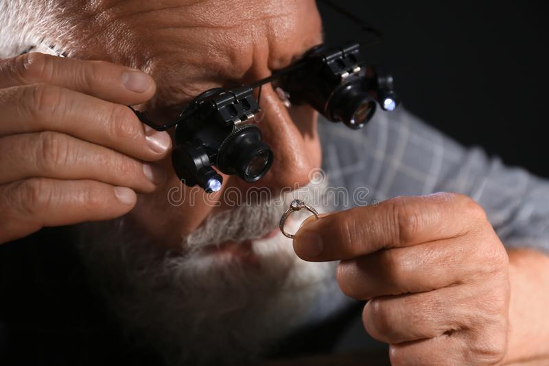 Male jeweler evaluating diamond ring in workshop. Closeup view stock photos