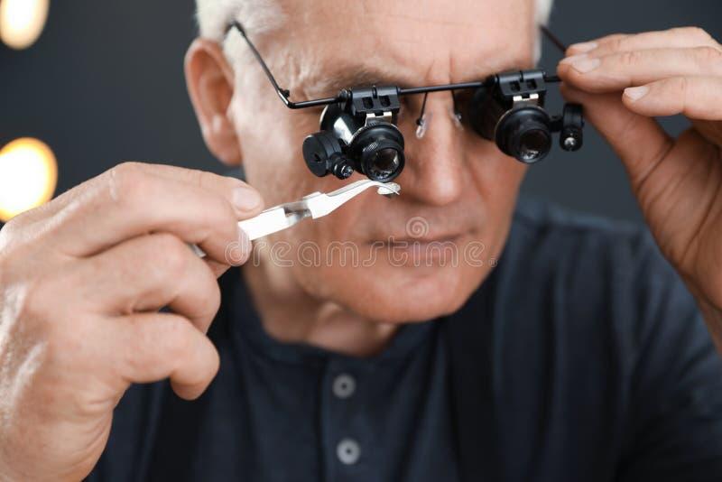 Male jeweler evaluating precious gemstone in workshop. Closeup royalty free stock photo