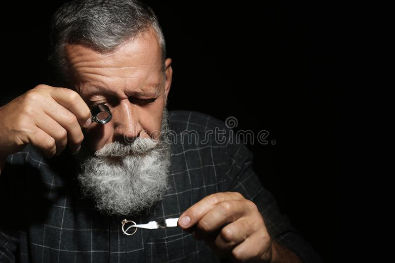 Male jeweler evaluating  ring in workshop, space for text. Male jeweler evaluating diamond ring in workshop, space for text stock image