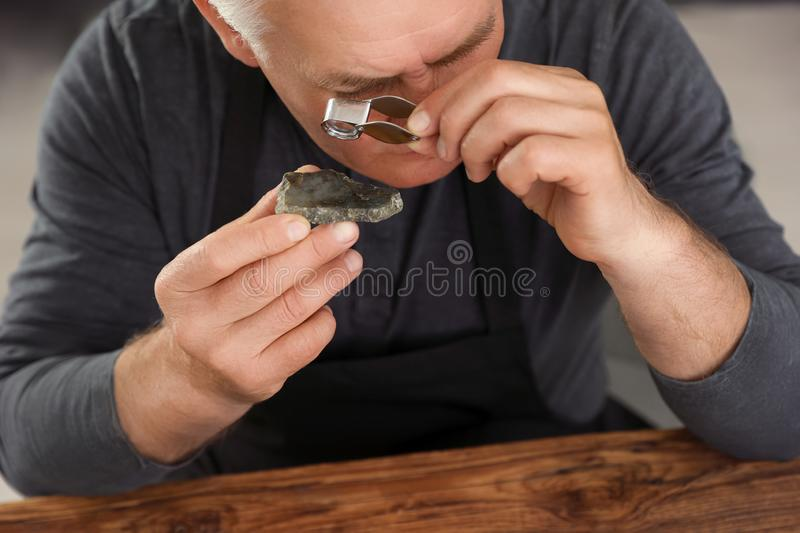 Male jeweler evaluating semi precious gemstone at table. In workshop stock photography