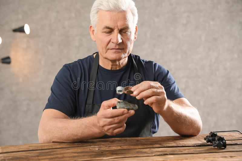Male jeweler evaluating semi precious gemstone at table. In workshop stock image