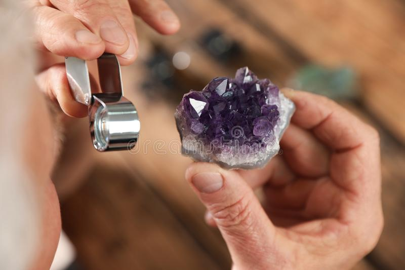 Male jeweler evaluating semi precious gemstone at table in workshop. Closeup stock photography